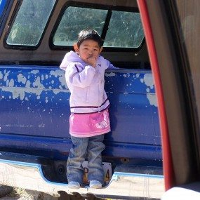 Navajo child on the back of car