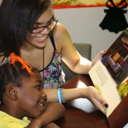teen reading donated book to low-income schoolgirl